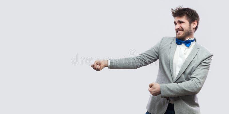 Portrait de vue de côté de profil de juger l'homme barbu bel dans le costume gris occasionnel et la position bleue de noeud papil photographie stock libre de droits