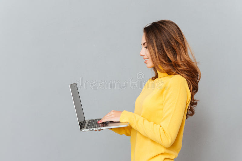 Portrait de vue de côté d'une femme gaie dactylographiant sur l'ordinateur portable photo libre de droits