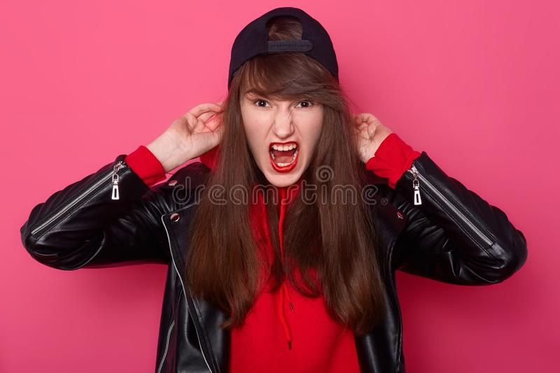 Portrait de vue de face de fille fâchée avec de longs cheveux et maquillage dans la position noire de veste en cuir de style occa photo stock