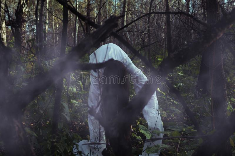 Portrait of a dead girl on Halloween in a gloomy forest. A ghost-girl in a gloomy dark forest at night on Halloween royalty free stock image