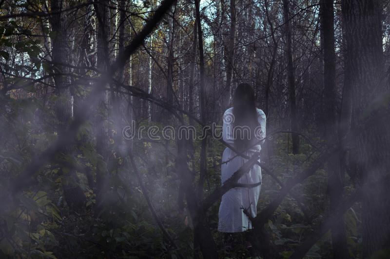 Portrait of a dead girl on Halloween in a gloomy forest. A ghost-girl in a gloomy dark forest at night on Halloween royalty free stock photos
