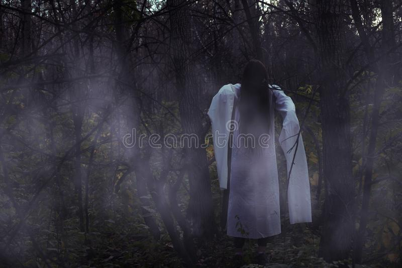 Portrait of a dead girl on Halloween in a gloomy forest. A ghost-girl in a gloomy dark forest at night on Halloween royalty free stock photo