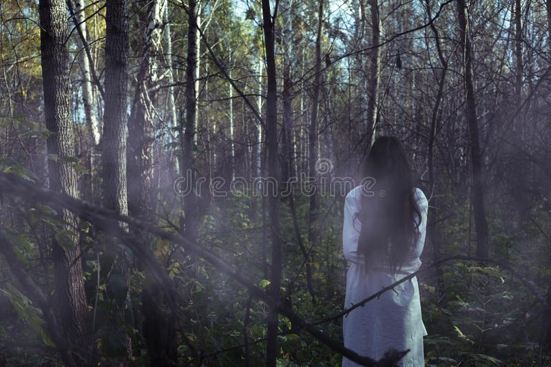 Portrait of a dead girl on Halloween in a gloomy forest. A ghost-girl in a gloomy dark forest at night on Halloween stock photo
