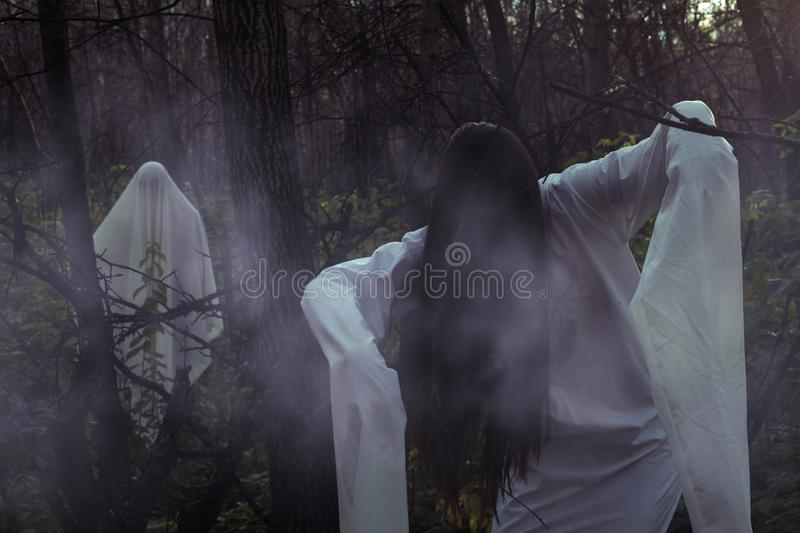 Portrait of a dead girl on Halloween in a gloomy forest. A ghost-girl in a gloomy dark forest at night on Halloween royalty free stock photography