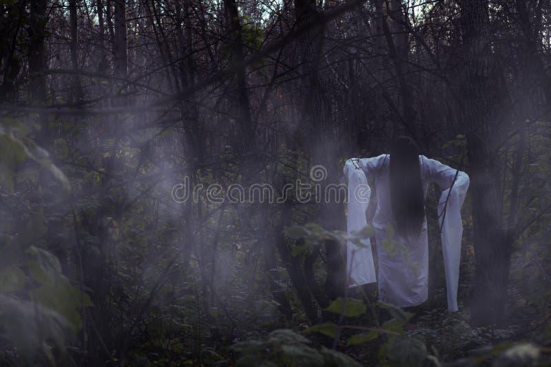 Portrait of a dead girl on Halloween in a gloomy forest. A ghost-girl in a gloomy dark forest at night on Halloween stock photos
