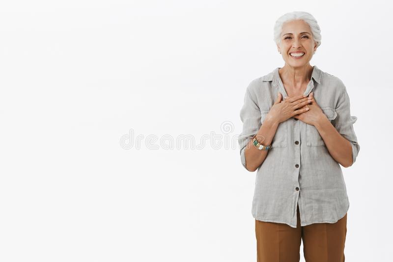 Portrait of delighted charming old female with grey combed hair holding palms on chest with pleased and grateful smile. Being delighted receiving warm stock photo