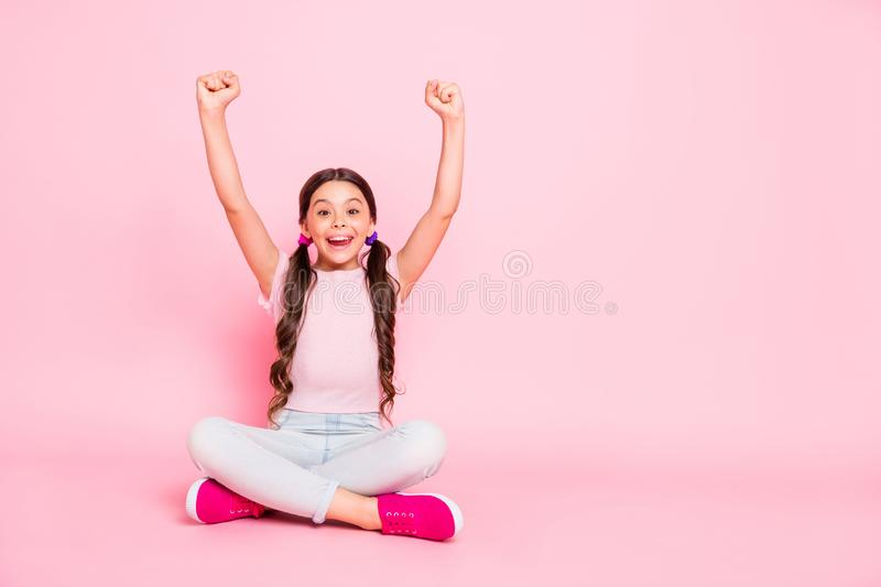 Portrait of delighted child raise fists scream shout yeah sitting dressed white pants trousers  over pink. Portrait of delighted child raise fists, scream shout stock images