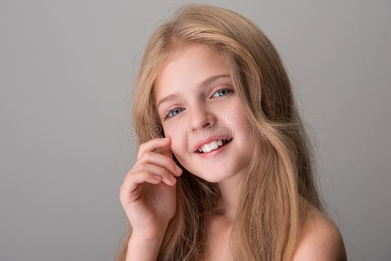 Happy adorable child is enjoying her skin. Portrait of delighted endearing little girl with naked shoulders and long hair is looking at camera with smile while stock image
