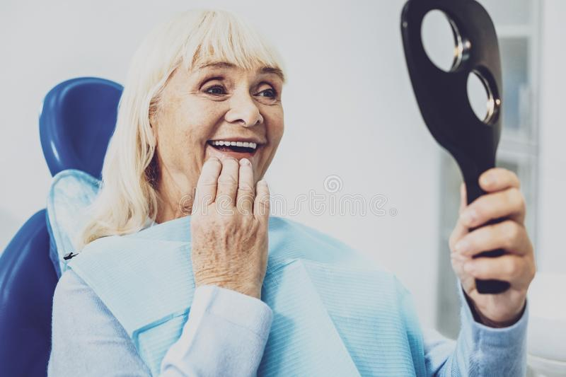 Portrait of delighted female that examining her teeth. I like it. Pretty retired woman keeping smile on her face while looking at the mirror royalty free stock images