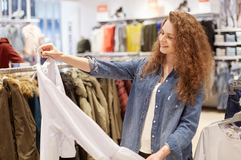 Portrait of delighted female spends weekend on shopping, chooses new blouse, strolls in fashionable boutique of clothes, dressed i stock image