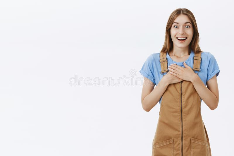 Portrait of delighted greatful charming kind young girl in brown overalls holding palms pressed to chest in thankful. Pose smiling from satisfaction and stock images
