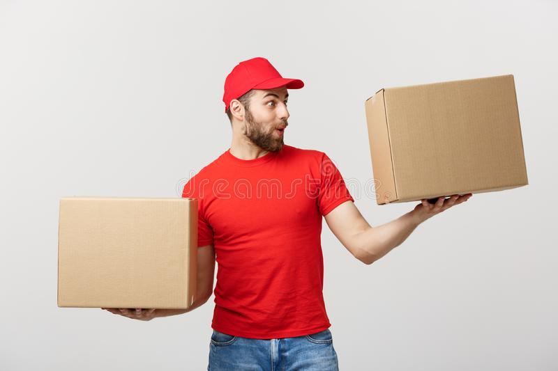 Portrait delivery man in cap with red t-shirt working as courier or dealer holding two empty cardboard boxes. Receiving royalty free stock photo