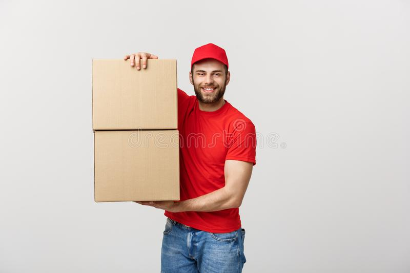 Portrait delivery man in cap with red t-shirt working as courier or dealer holding two empty cardboard boxes. Receiving royalty free stock photography