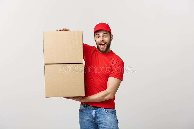 Portrait delivery man in cap with red t-shirt working as courier or dealer holding two empty cardboard boxes. Receiving. Package. Copy space for advertisement stock photo