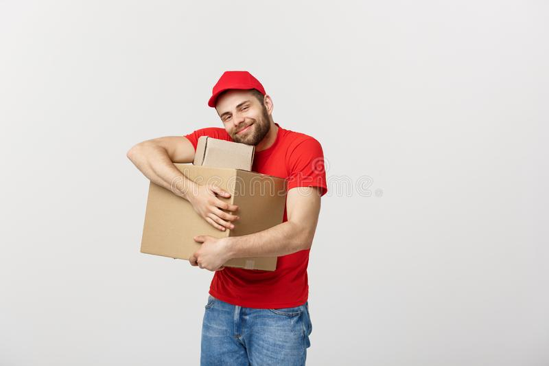 Portrait delivery man in cap with red t-shirt working as courier or dealer holding two empty cardboard boxes. Receiving stock images