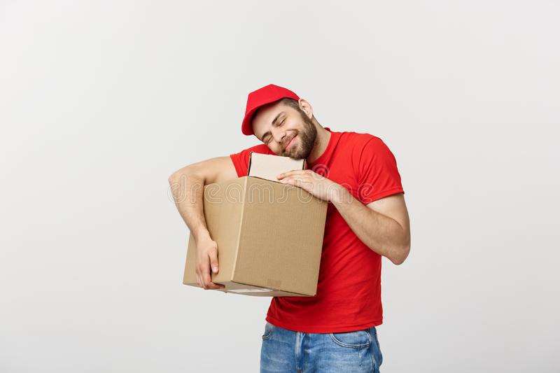 Portrait delivery man in cap with red t-shirt working as courier or dealer holding two empty cardboard boxes. Receiving royalty free stock image