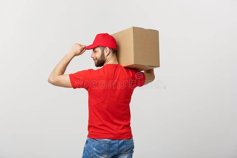 Portrait delivery man in cap with red t-shirt working as courier or dealer holding two empty cardboard boxes. Receiving royalty free stock photos