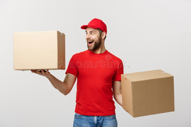 Portrait delivery man in cap with red t-shirt working as courier or dealer holding two empty cardboard boxes. Receiving stock photos