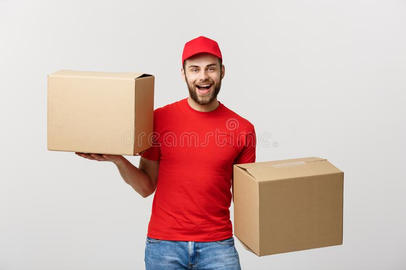 Portrait delivery man in cap with red t-shirt working as courier or dealer holding two empty cardboard boxes. Receiving. Package. Copy space for advertisement royalty free stock photo