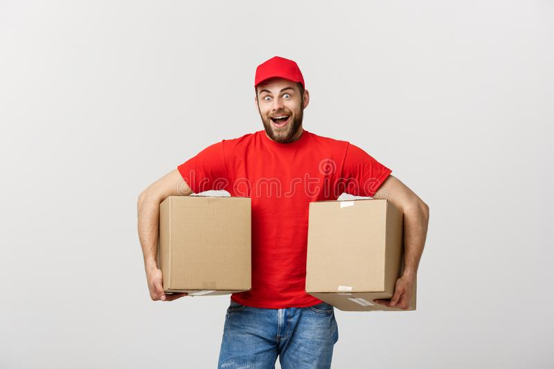 Portrait delivery man in cap with red t-shirt working as courier or dealer holding two empty cardboard boxes. Receiving. Package. Copy space for advertisement royalty free stock photos