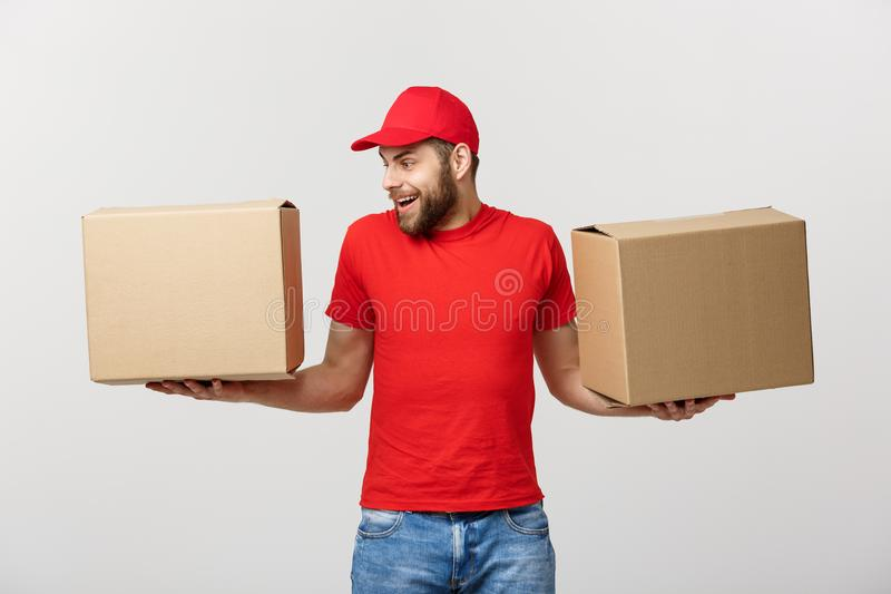 Portrait delivery man in cap with red t-shirt working as courier or dealer holding two empty cardboard boxes. Receiving. Package. Copy space for advertisement stock photography