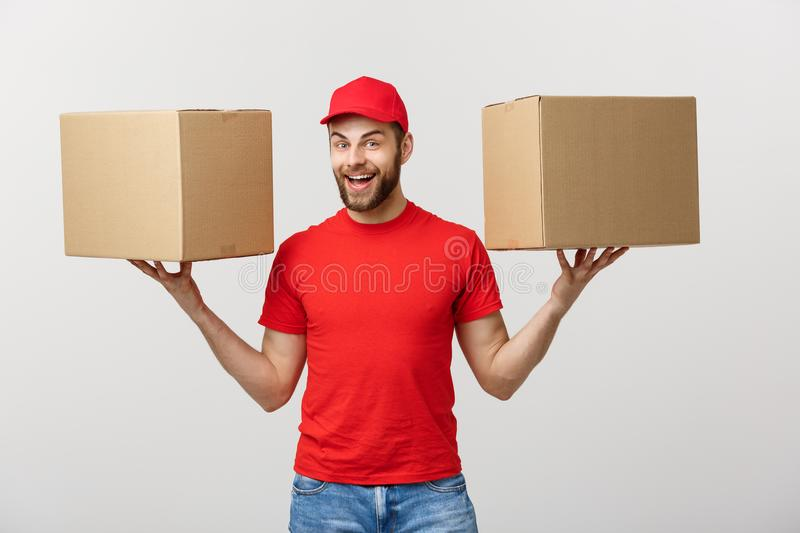 Portrait delivery man in cap with red t-shirt working as courier or dealer holding two empty cardboard boxes. Receiving. Package. Copy space for advertisement stock image