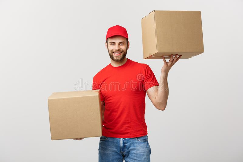 Portrait delivery man in cap with red t-shirt working as courier or dealer holding two empty cardboard boxes. Receiving. Package. Copy space for advertisement royalty free stock images