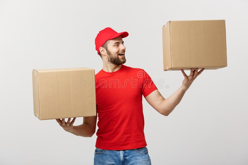 Portrait delivery man in cap with red t-shirt working as courier or dealer holding two empty cardboard boxes. Receiving stock photo
