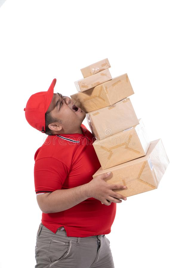 Portrait of delivery man struggling to lift many boxes royalty free stock images