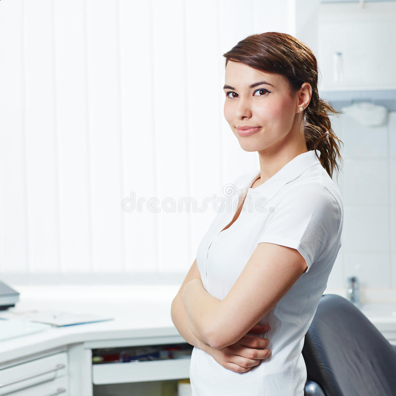 Portrait of dental assistant with arms crossed. Portrait of an attractive dental assistant with her arms crossed in dental practice stock image
