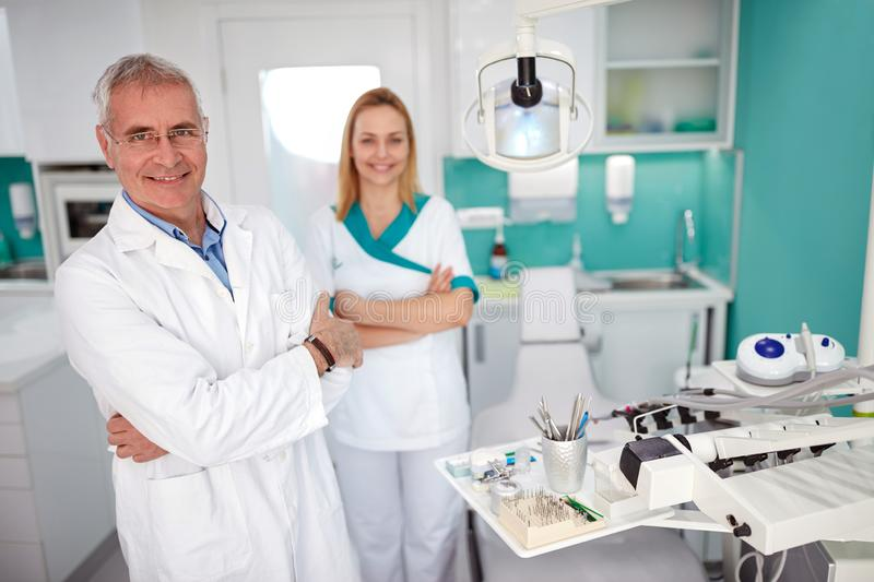 Portrait of dentist with female assistant in dental practice. Portrait of senior dentist with nice female assistant in dental practice royalty free stock images