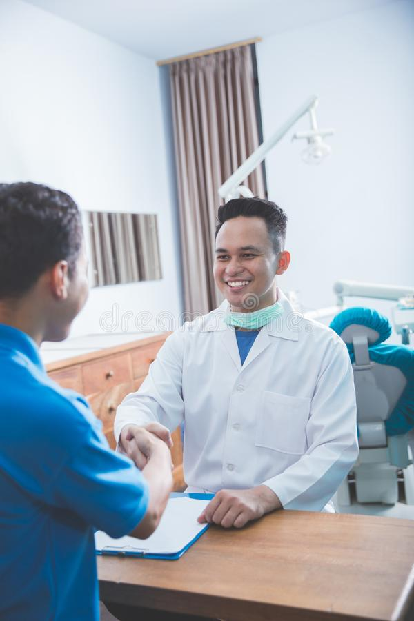 Dentist talking to his patient at dental care clinic and shaking. Portrait of dentist talking to his patient at dental care clinic and shaking hands royalty free stock images
