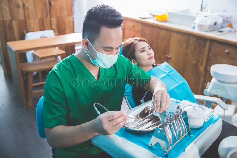 Dentist taking care of female patient. Portrait of a dentist who treats teeth of young women patient stock photography