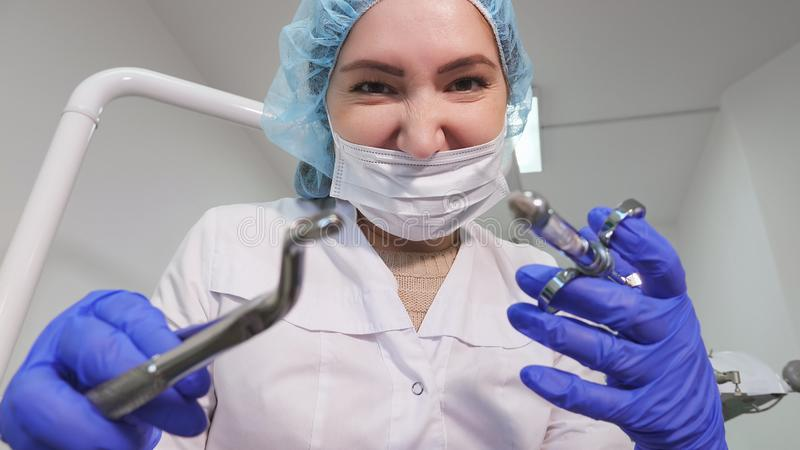 Dentist woman doctor is holding dental instruments forceps and needle in hands and looking at camera. Portrait of dentist woman doctor in uniform is holding royalty free stock image
