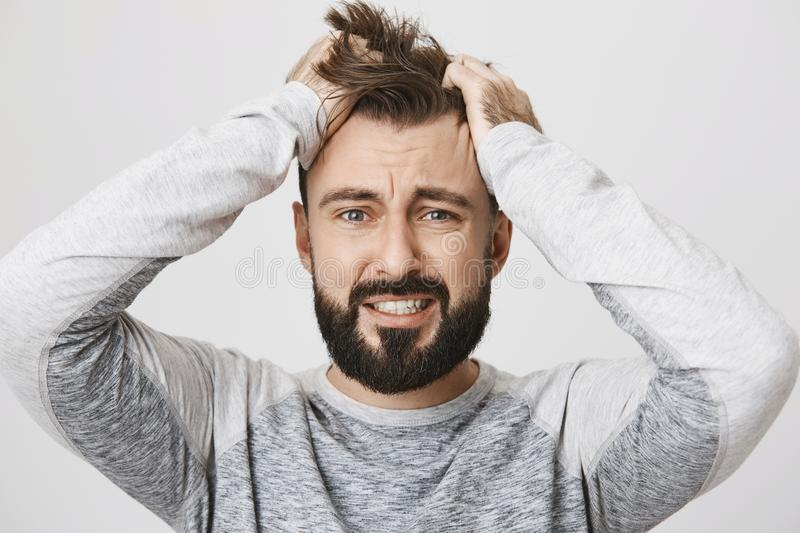 Portrait of depressed bearded guy feeling pressure, grabbing hair with hands and expressing devastation, standing over stock photos