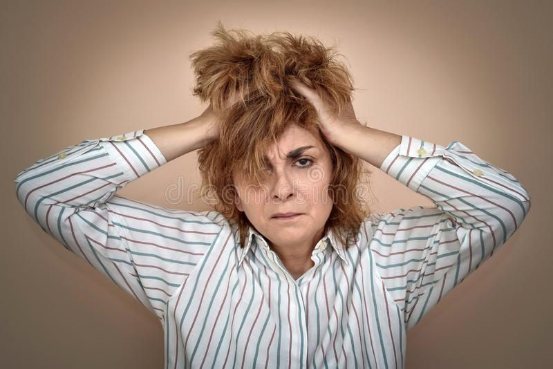 Portrait of depressed and desperate middle-aged woman. With hands on her hair stock photo