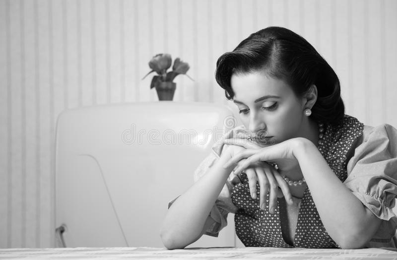 Housewife sad. Portrait of a depressed housewife in the kitchen stock photo