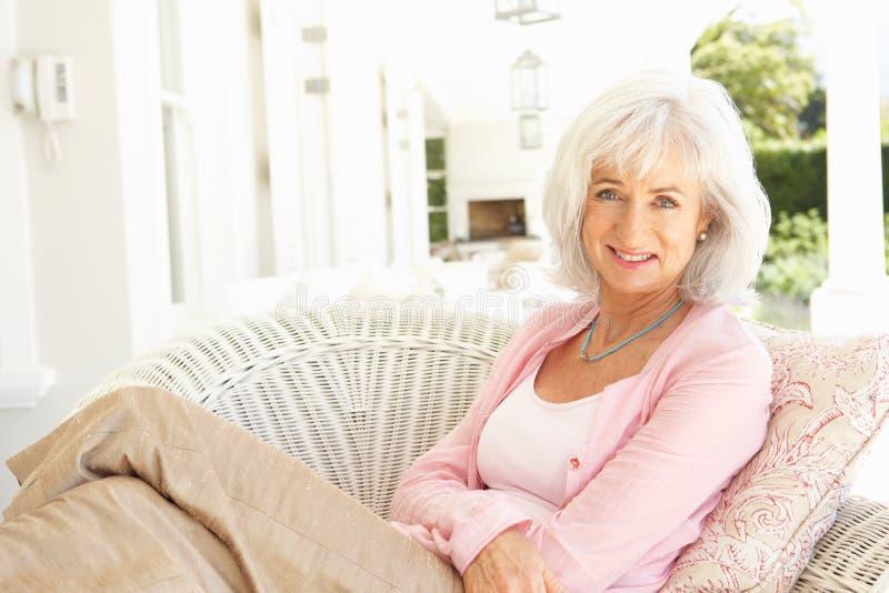 Portrait der älteren Frau entspannend im Stuhl stockbild