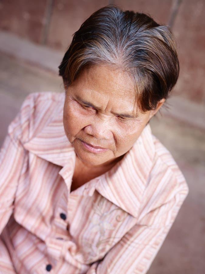 Portrait der alten asiatischen Frau, die Kamera betrachtet stockfoto