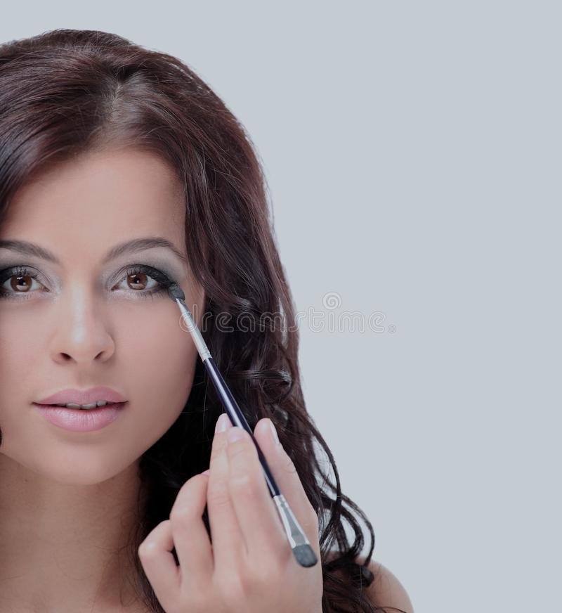 Portrait der attraktiven jungen erwachsenen Frau, die Blusher anwendet stockfotografie