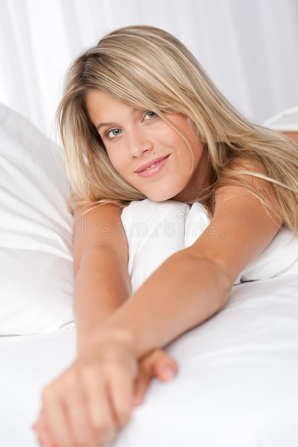 Portrait der blonden Frau liegend im Bett stockbilder