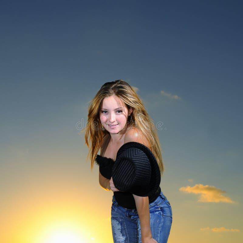 Portrait der blonden jugendlich Aufstellung über Sonnenunterganghimmel lizenzfreies stockfoto