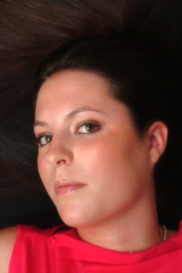 Portrait der Brunette-Frau liegend auf Fußboden stockfoto