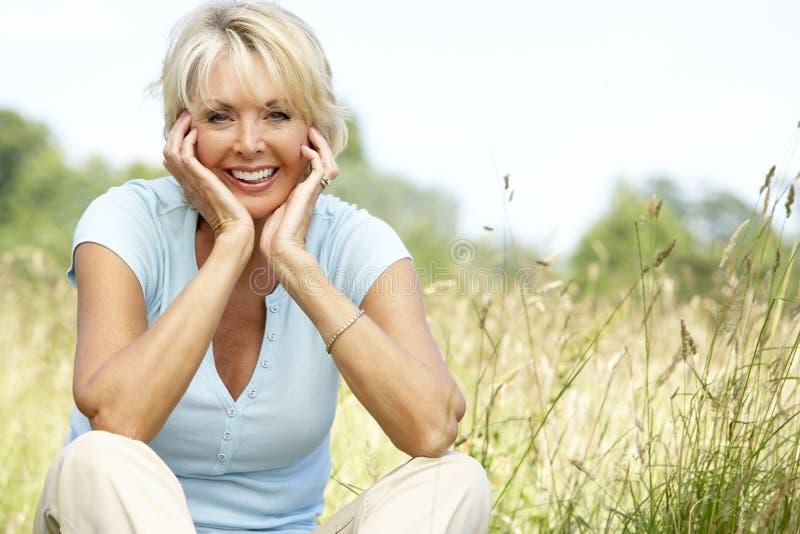 Portrait der fälligen Frau sitzend in der Landschaft stockbild