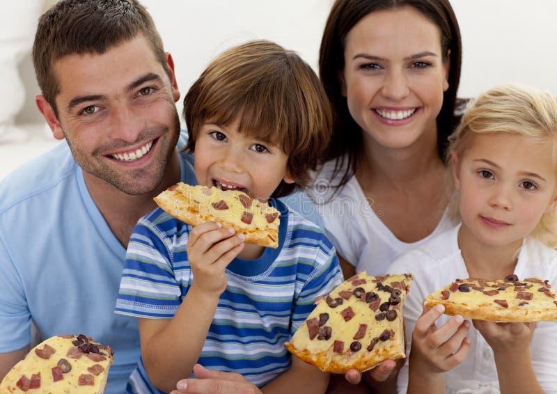 Portrait der Familie Pizza im Wohnzimmer essend lizenzfreies stockfoto