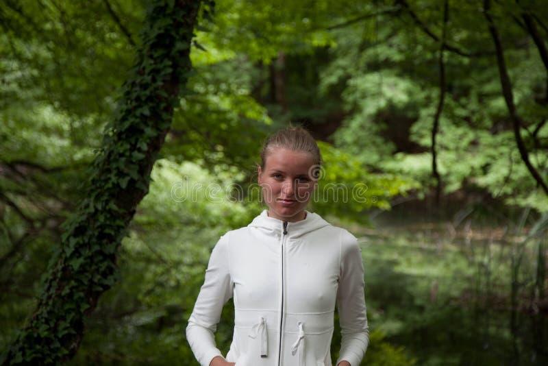 Portrait der Frau in der weißen Strickjacke auf Grün stockbild