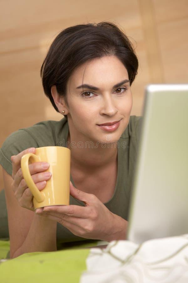 Portrait der Frau, die Kaffee im Bett trinkt lizenzfreie stockbilder