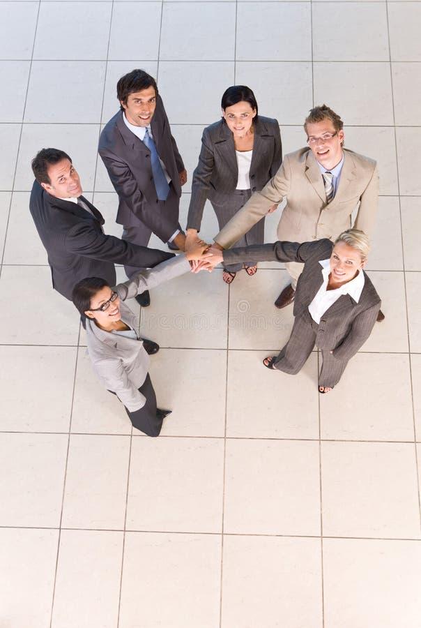 Portrait der Geschäftsleute, die Hände anhalten lizenzfreie stockfotos
