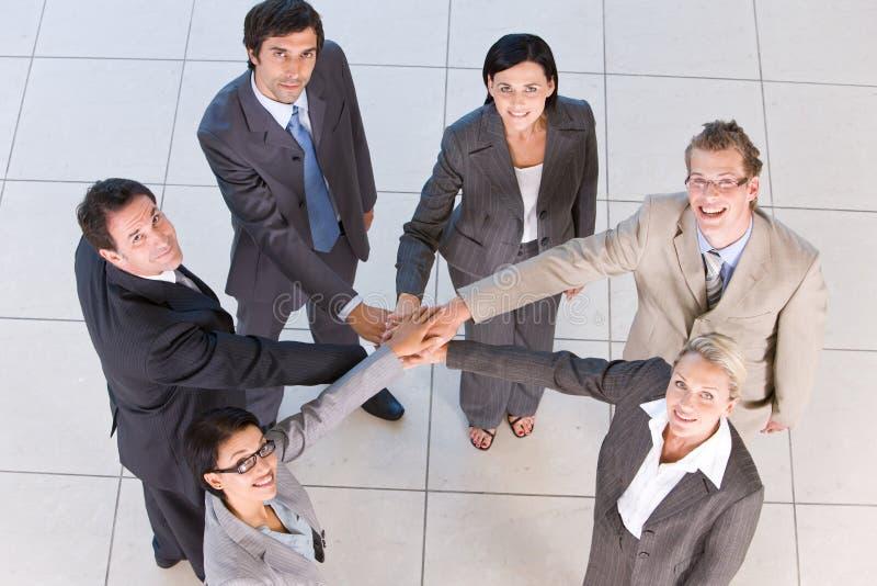 Portrait der Geschäftsleute, die Hände anhalten lizenzfreie stockfotografie