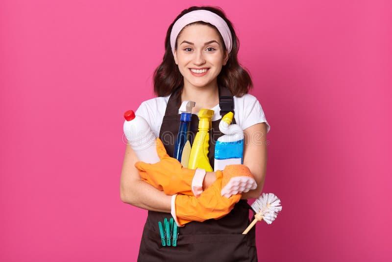 Portrait der glücklichen Hausfrau, die orangefarbene Gummihandschuhe trägt, die Waschmittelflaschen und -staubflaschen bei der Ha stockbild